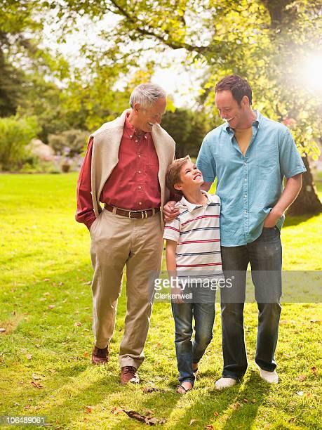 Men with a boy (4-5) walking together at park