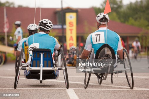 Men with a spinal cord injury and Veteran leg amputee participating in a handcycle race : Stock Photo