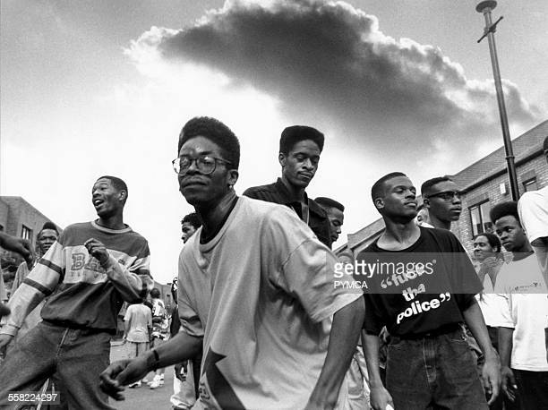 Men with flat top haircuts dancing in the street as an ominous storm cloud rolls overhead Notting Hill Carnival London UK 1980s