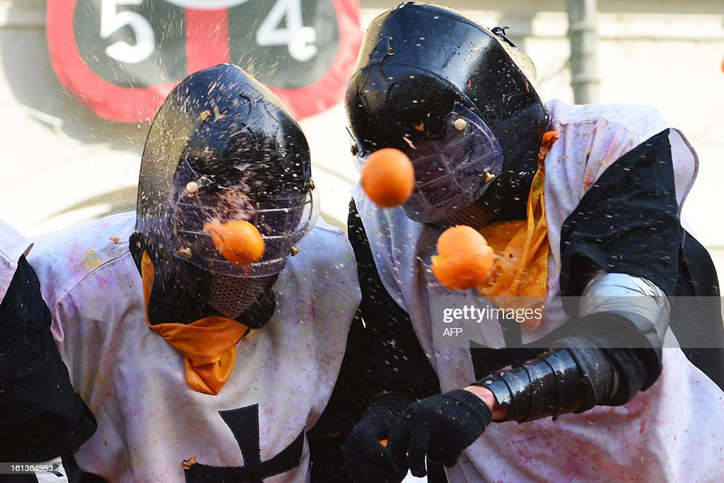 Men with helmets are hit by oranges during the traditional 'battle of the oranges' held during the carnival in Ivrea, near Turin, on February 10, 2013. During the event which marks the people's rebellion against tyrannical lords who ruled the town in the Middle Ages, revellers parading on floats represent guards of the tyrant, while those on foot the townsfolk.
