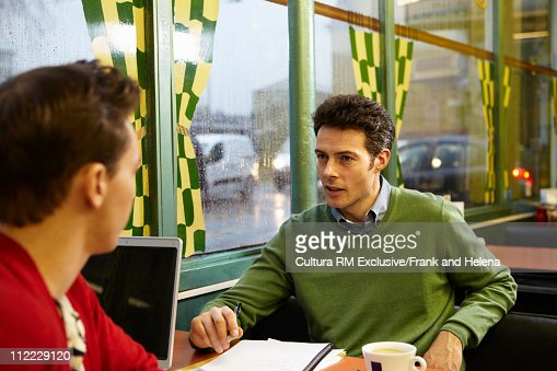 2 men with laptop in cafe on a rainy day : Stock Photo