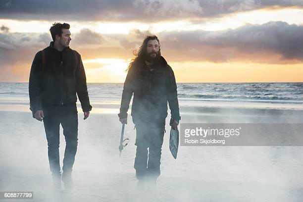 Men with speargun and fish walking on beach