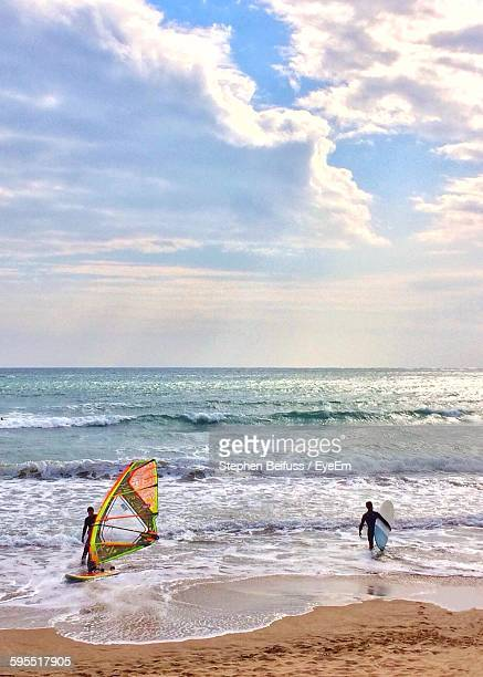Men With Surfboards At Beach Against Sky