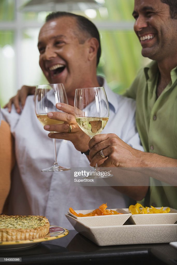 Men with wine laughing in kitchen : Stock Photo