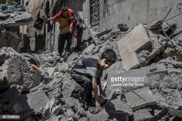 Men women and children emerge from the rubble of alNuri mosque complex on June 29 in Mosul IraqThe Iraqi Army Special Operations Forces and...