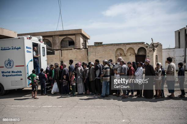 Men women and children queue to be treated at a mobile clinic during fighting in west Mosul on April 8 2017 in Mosul Iraq Despite air support from...