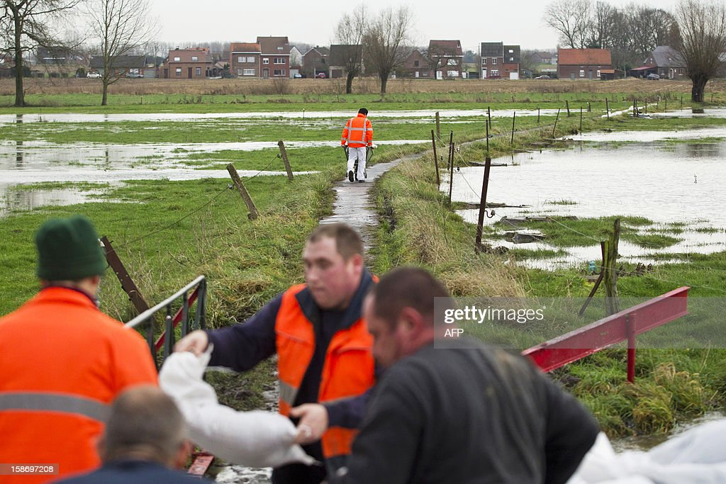 Men work at placing sand bags to block an overflowing stream during a state of emergency in Londerzeel where heavy rains have caused high tides and floods, on December 24, 2012.