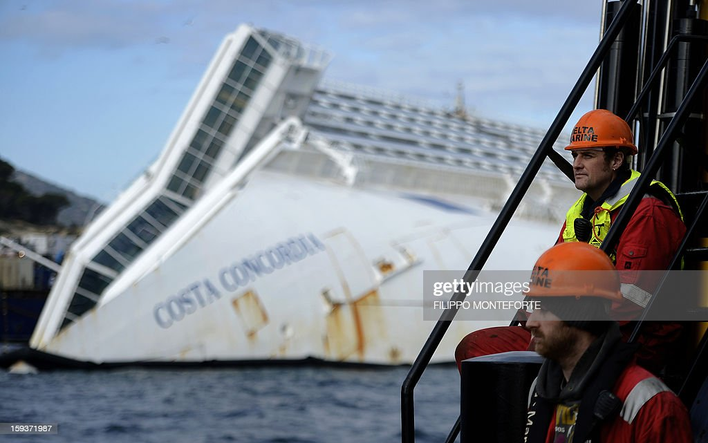 Men work in front of the Costa Concordia cruise ship laying aground outside the port the western Italian island of Giglio on January 12, 2013. A year after the Costa Concordia tragedy in which 32 people lost their lives, the giant cruise ship still lies keeled over on an Italian island and its captain Francesco Schettino has become a global figure of mockery.