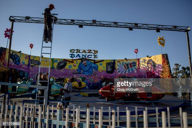 Men work on fixing a ride at the Mosul Amusement Park on November 4 2017 in Mosul Iraq The theme park was shut down under ISIS occupation and the...