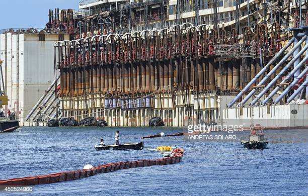 Men work on floating booms near the refloated wreck of the Costa Concordia cruise ship in front of the harbour of Isola del Giglio after it was...