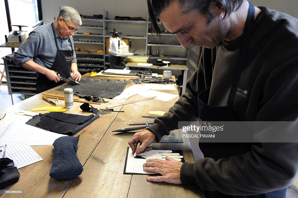 CLAVEL - Men work on making gloves on January 9, 2013, in Millau, at the Causse glove factory. The French company founded in 1892 was bought in late September by Chanel through its Paraffection subsidiary dedicated to high-quality craftsmanship and handicraft work. AFP PHOTO / PASCAL PAVANI