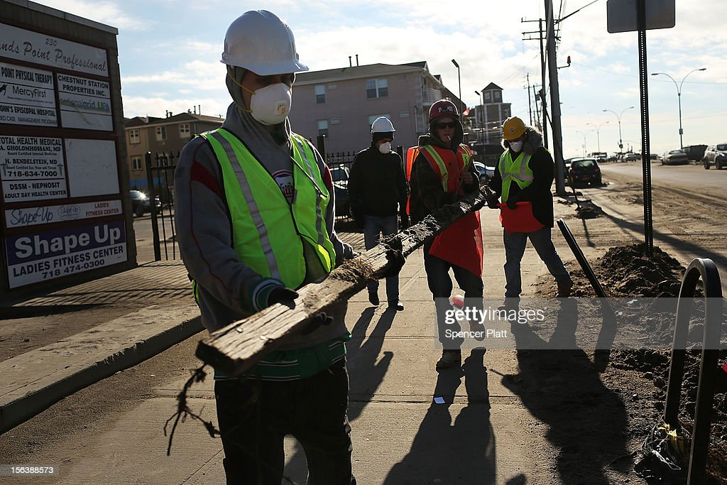 Men work on the clean-up in the heavily damaged Rockaway neighborhood where a large section of the iconic boardwalk was washed away on November 14, 2012 in the Queens borough of New York City. Two weeks after Superstorm Sandy slammed into parts of New York and New Jersey, thousands are still without power and heat.