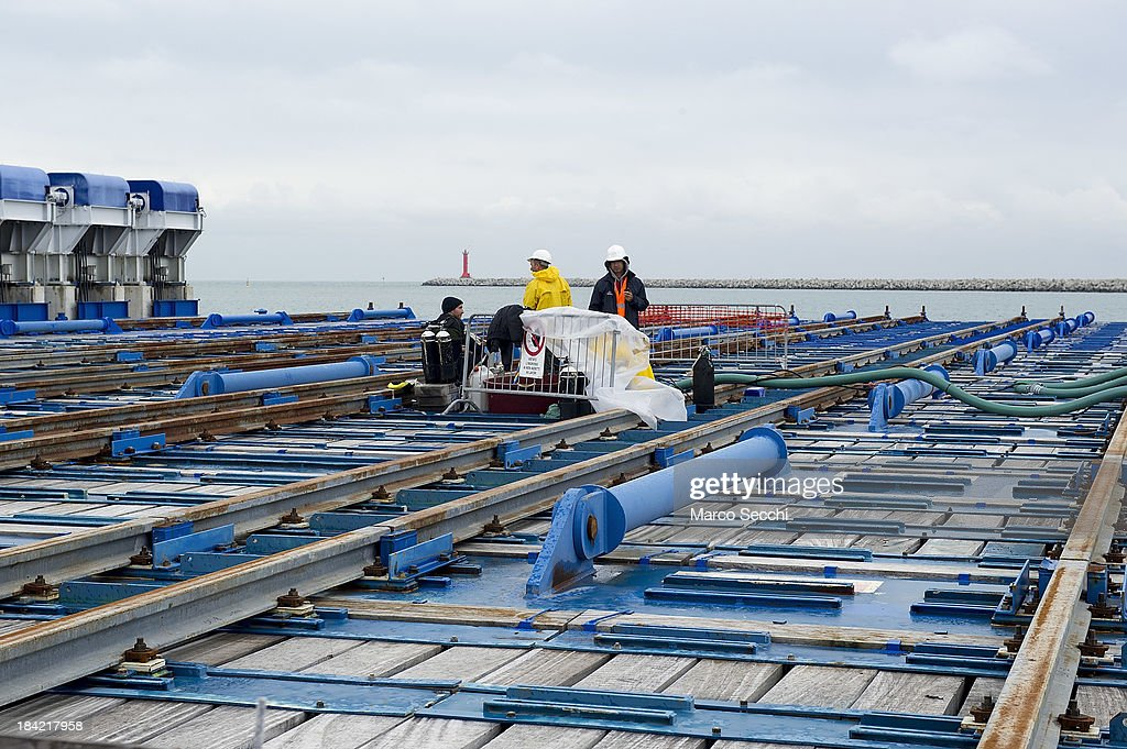 Men work on the the Rolls-Royce syncrolit barge for the giant seabed caissons on October 12, 2013 in Venice, Italy. The Mose project works towards protecting Venice from high tides and flooding.