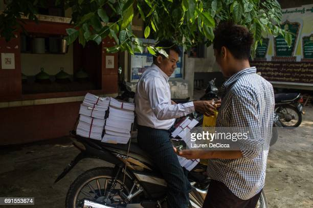 Men work to pack the monthly magazine distributed by the Masoeyein Monastery home of Wirathu into a motorbike for delivery on June 1 2017 in Mandalay...
