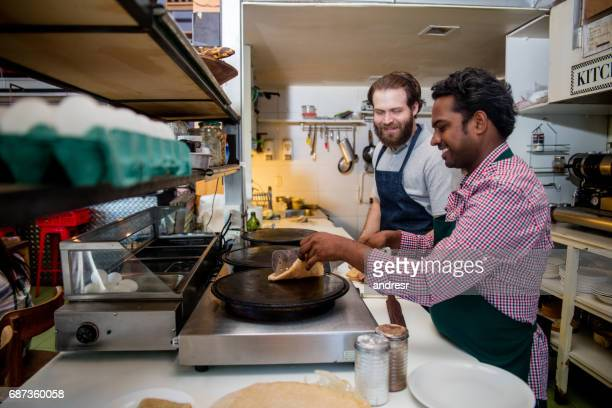 Men working at a restaurant making crepes