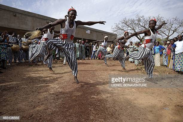 Men working in the French cosmetics company L'Occitane butter shea production line dance during a welcoming ceremony on January 24 2014 in Leo...