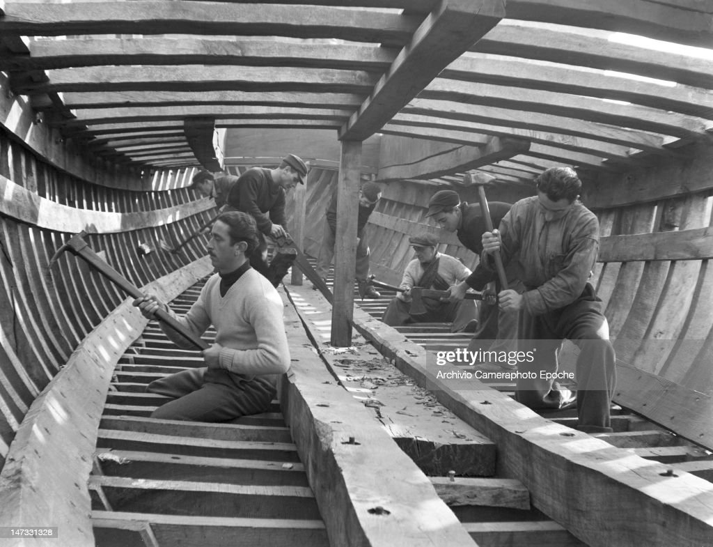 men working inside a wooden sail boat frame chioggia venice 1950
