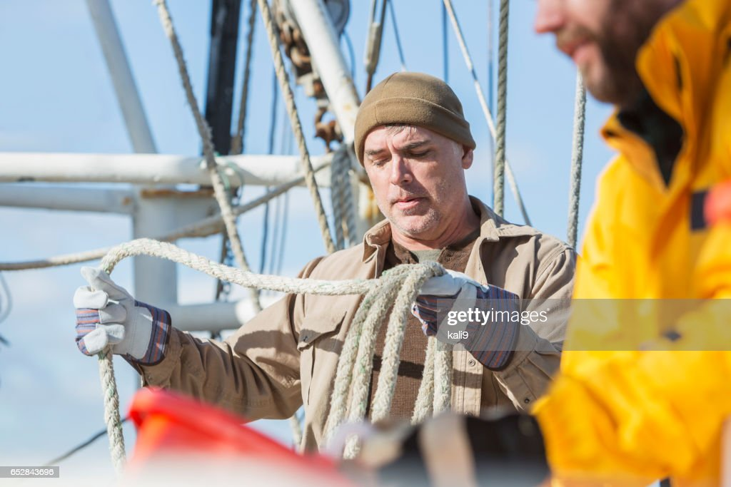 Men working on commercial fishing boat : Stockfoto
