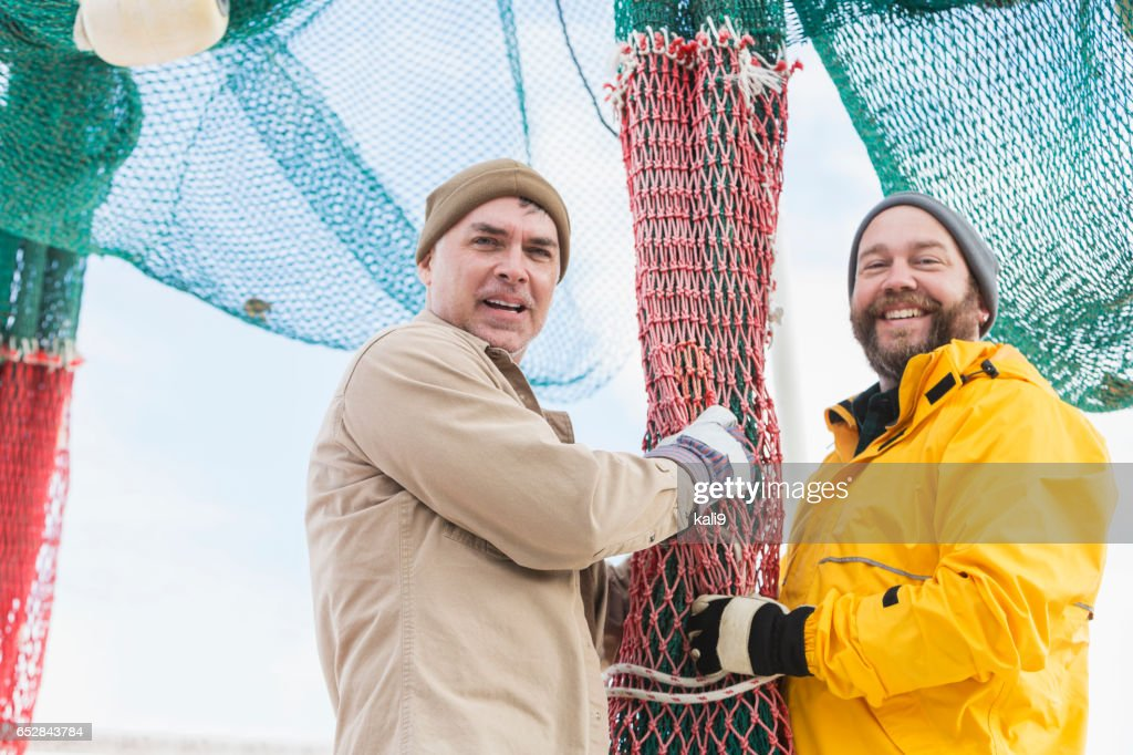 Men working on commercial fishing boat preparing nets : Stock Photo