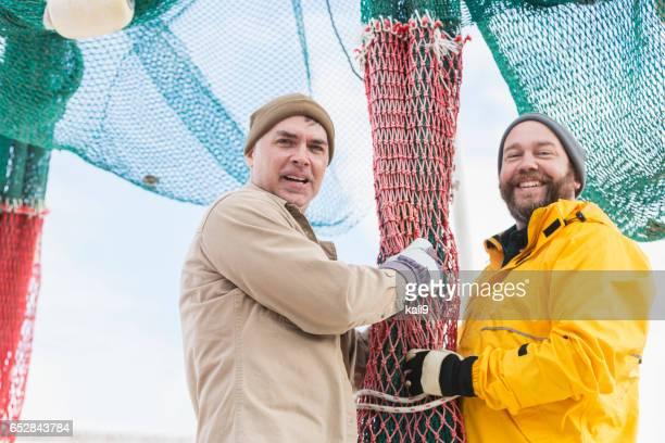 Men working on commercial fishing boat preparing nets