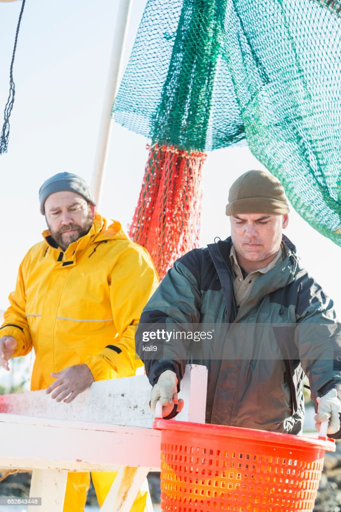 Men working on commercial shrimp boat unloading basket : Stock Photo