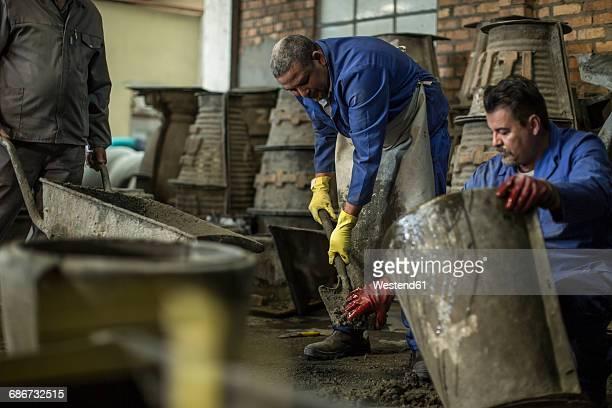 Men working together in industrial pot factory