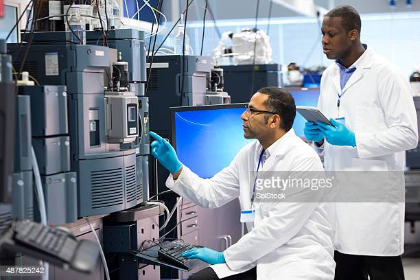 Men Working With Specialist Scientific Equipment for Measuring Chemicals.