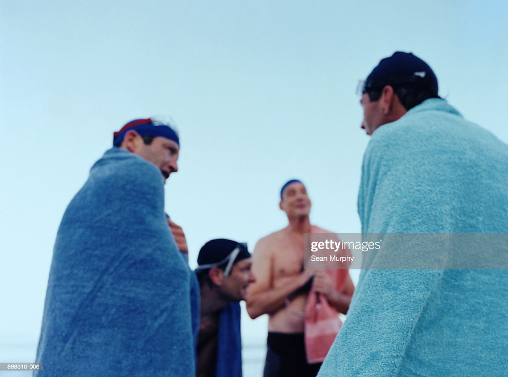 Men wrapped in towels after swimming in ocean (defocussed) : Stock Photo