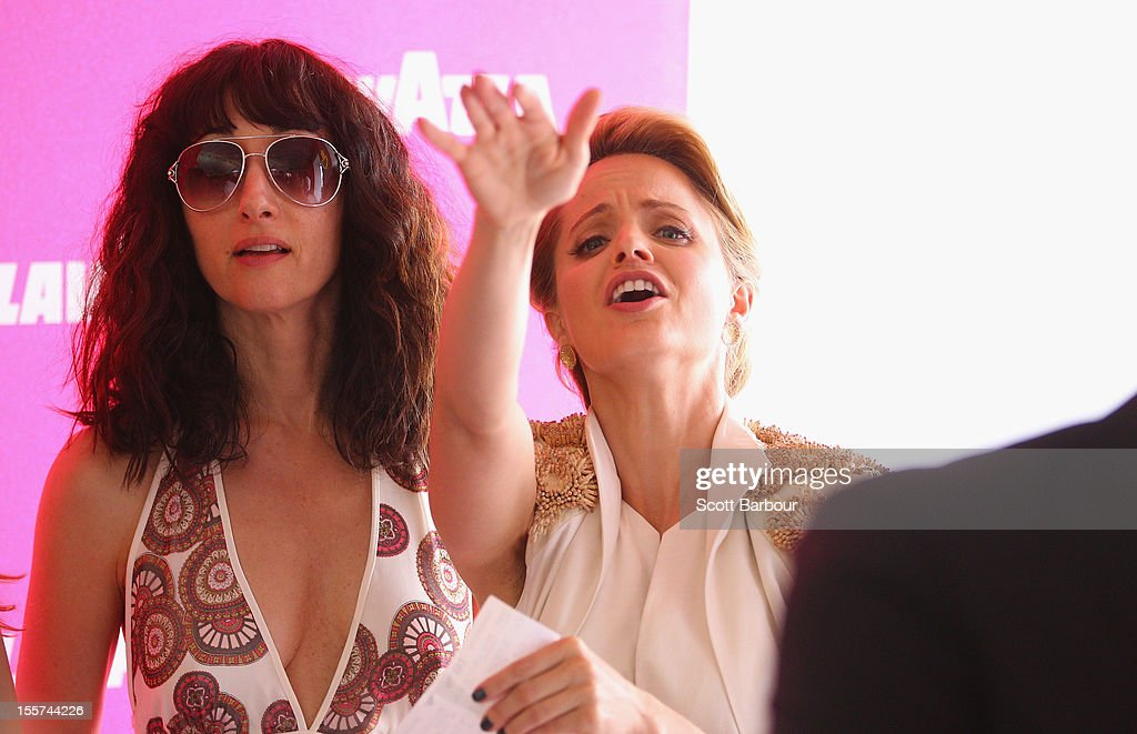 Mena Suvari (R) watches a horse race that she has gambled on in the Lavazza marquee on Crown Oaks Day at Flemington Racecourse on November 8, 2012 in Melbourne, Australia.