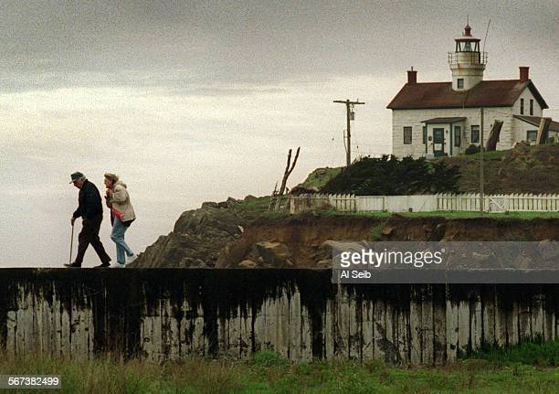 MENorthCoast#1AS12–17–96B Crescent City CA Del Norte County Warren Ivers with his wife Catherine walk in front of the landmark Battery Point...