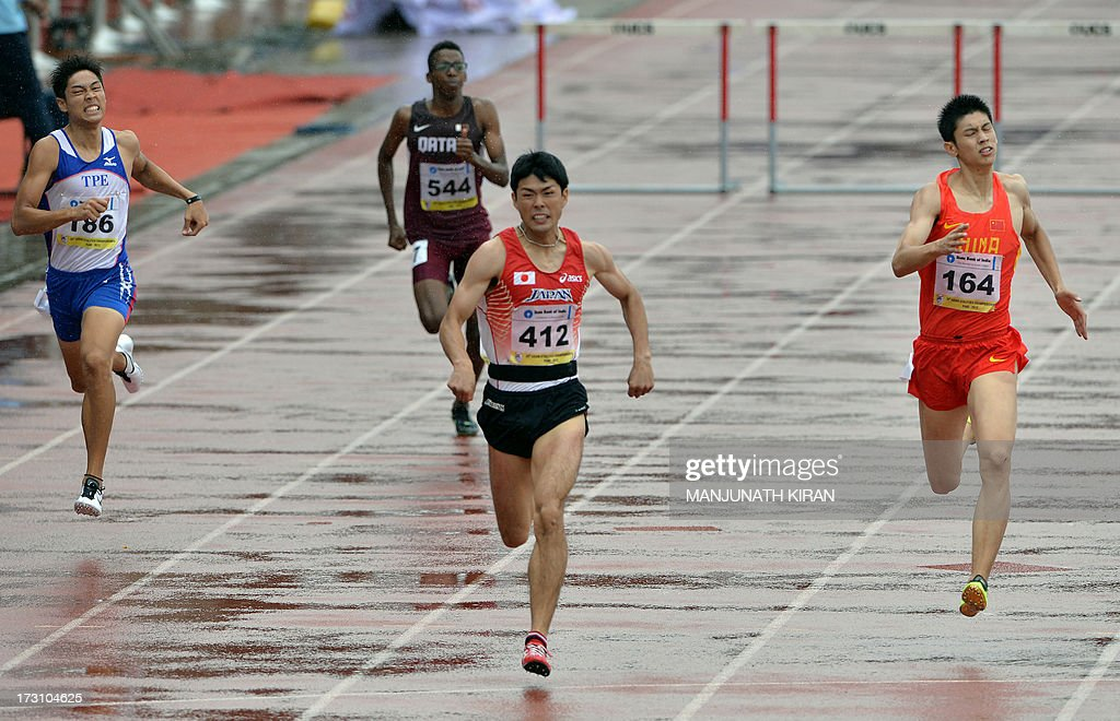 Men's 400 meter hurdles gold medal winner from Japan Yasuhiro Fueki (2R) and silver medalist from China Cheng Wen (R) race towards the finish line on the fifth and the final day of the Asian Athletics Championship 2013 at the Chatrapati Shivaji Stadium in Pune on July 7, 2013. AFP PHOTO/Manjunath KIRAN