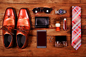 Variety of men's accessories organized in knolling arrangement.  Items include: dress shoes, tie, sunglasses, wallet, watch, shaving brush, cologne, and smart phone.  The items all lie on a wooden des