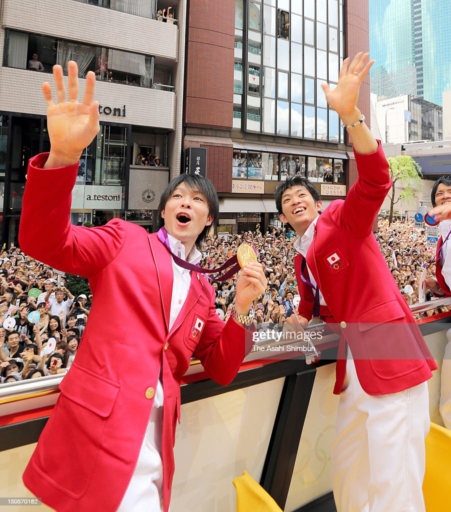 Men's Artistic Gymanstics individual all-around gold medalist <a gi-track='captionPersonalityLinkClicked' href=/galleries/search?phrase=Kohei+Uchimura&family=editorial&specificpeople=5481263 ng-click='$event.stopPropagation()'>Kohei Uchimura</a> and Men's Artistic Gymnastics Team Silver medalist <a gi-track='captionPersonalityLinkClicked' href=/galleries/search?phrase=Kazuhito+Tanaka&family=editorial&specificpeople=4950263 ng-click='$event.stopPropagation()'>Kazuhito Tanaka</a> wave to the crowds from an open-top bus during Japanfs Olympic medalists parade in streets of Ginzaon August 20, 2012 in Tokyo, Japan. An estimated 500,000 people gathered to see the 38 medal winners.