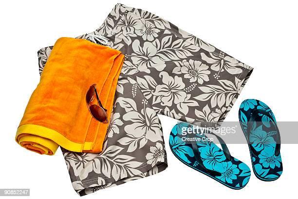 Men's beach shorts, flip flips, towel and sunglass
