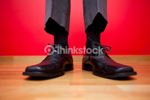 Men's business loafers standing on hardwood on a red wall : Stock Photo
