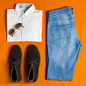 flat lay men's clothing on orange background
