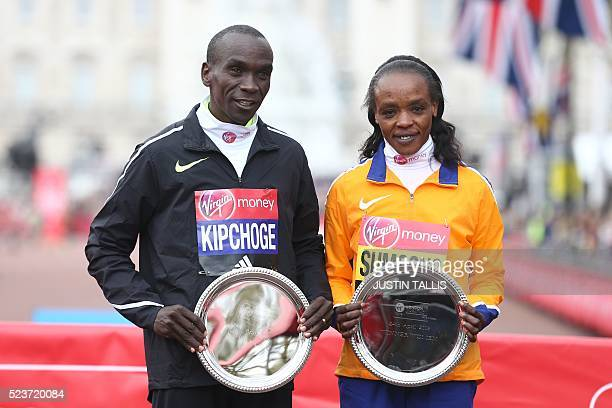 Men's elite race winner Kenya's Eliud Kipchoge and women's elite race winner Kenyas Jemima Sumgong pose during the winners presentations for the...
