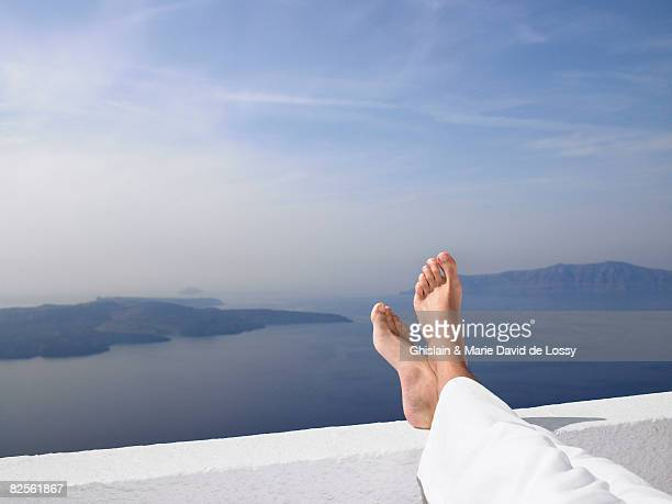 Men's feet on a low wall,  sea view