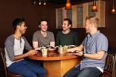 Diverse Group of Men in a Bible Study at a Cafe