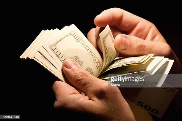 men's hands with dollar bills