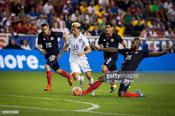 US Men's National Team Lee Nguyen drives forward against a sea of black uniforms that is the Costa Rica players David Guzman Johnny Acosta and...
