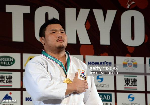 Men's over 100kg class gold medalist Kim SungMin of South Korea listens to the national anthem on the podium in the Grand Slam Tokyo 2013 judo...