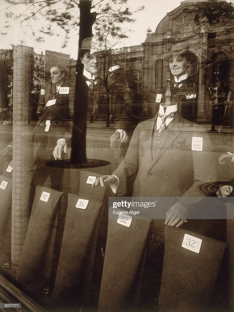 Men's pants and mannequins in men's suits in a window display of a men's clothing store, with the building across the street reflected in the window. Photograph by French photographer Eugene Atget, titled 'Magasin, Avenue des Gobelins.'