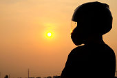 Men's silhouette wearing a helmet looking towards the goal ahead. On a sunset background