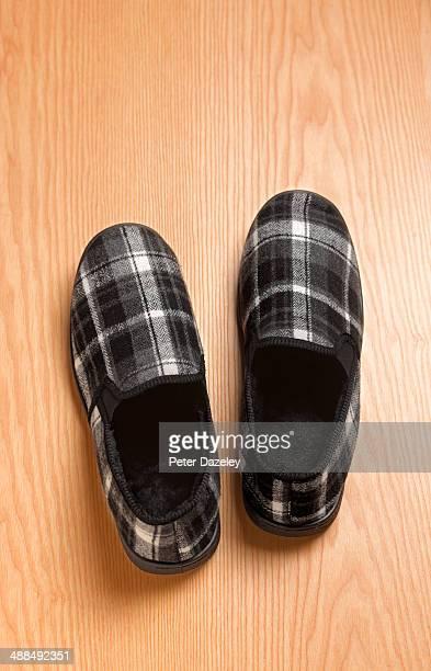 Men's slipper on wooden floor