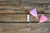 Menstrual cup and tampons on old wooden background. Top view.