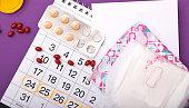 Menstruation calendar with sanitary pads and pills .Woman menstruation days