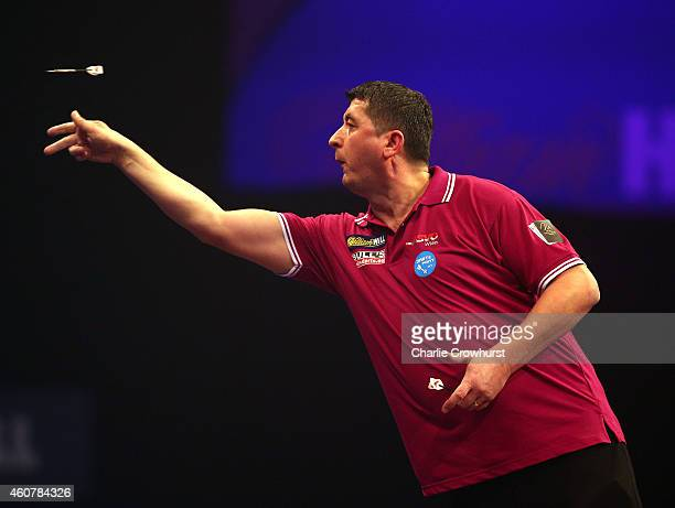 Mensur Suljovic of Austria in action during his first round match against Michael Smith of England during the William Hill PDC World Darts...