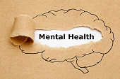 Text Mental Health appearing behind torn brown paper with drawn human brain on it.
