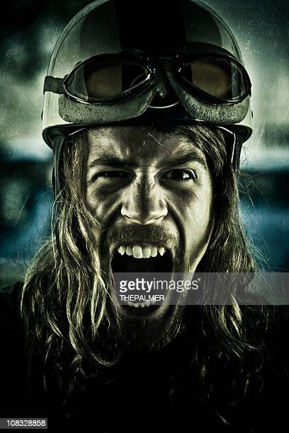 mental young motorcyclist screaming with vintage helmet